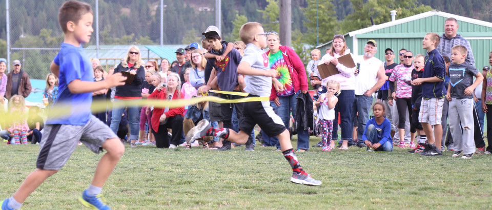 Owen Chatigny breaks the tape in the dash event at the Junior Olympics Saturday. A crowd of volunteers and spectators cheer him on.