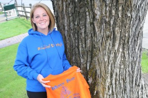 Kristin Compton displays this year's Muddy Butt race apparel. The race is Sunday at Xmas Hills Recreation area. Only blue hooded-sweatshirts will be available at the race.