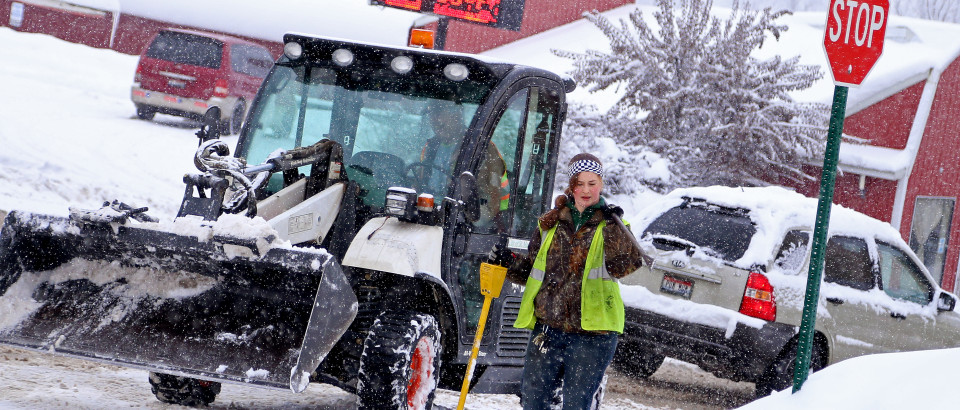 As snow continues to fall Jan. 10, Greg Reed and Jennifer Sheerer work to unblock drop drains along Main Ave. The city wants to keep the drains open to prevent flooding when the snow thaws.