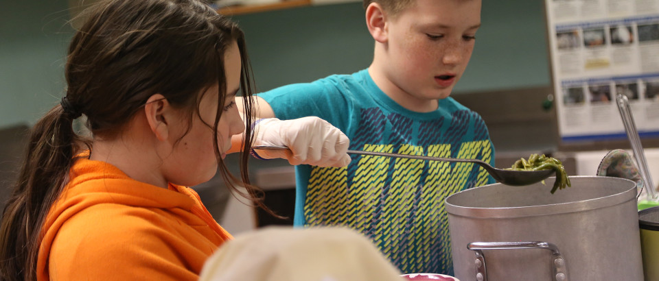 Raeleen McDonald and Kyler Jackson dish up string beans at a fundraiser for the Kiwanis April 3.