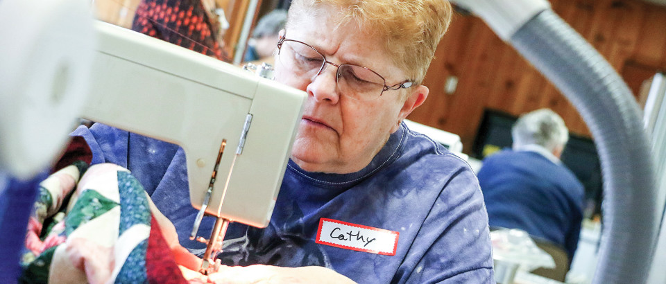 Cathy Buell runs her project through the sewing machine.