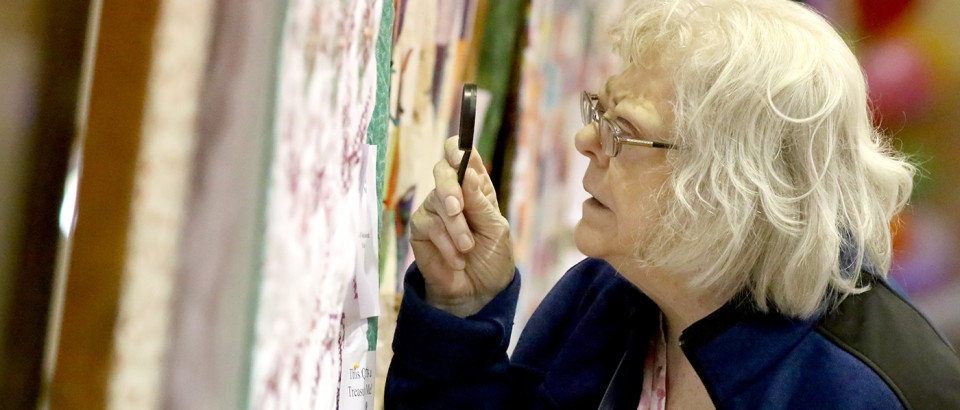 Sharon Stewart uses a magnify glass to study stitching on a quilt.