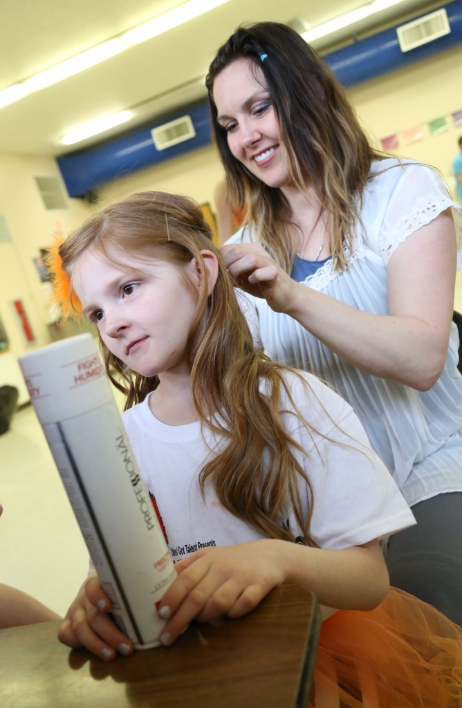 Tara Truscott curls her daughter Addison's hair before the performance.