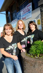 Shirley Ackerman, Kristin Compton and Amy Reid-Scheer sport race shirts in front of the Eagles, where the awards banquet will conclude the second annual Race the Joe this weekend.