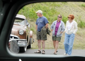 Mike Stroh, Cathy Britschgi and Aysan Tyrrell walk through a lineup of rat rods during the 2013 show.