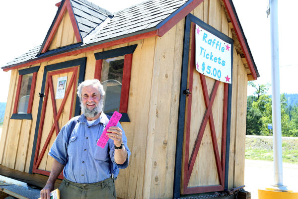 Steve Cuvala, a board member for the Benewah Valley Association, has raffle tickets to sell for the playhouse behind him. The winner will be drawn at the annual picnic July 12.