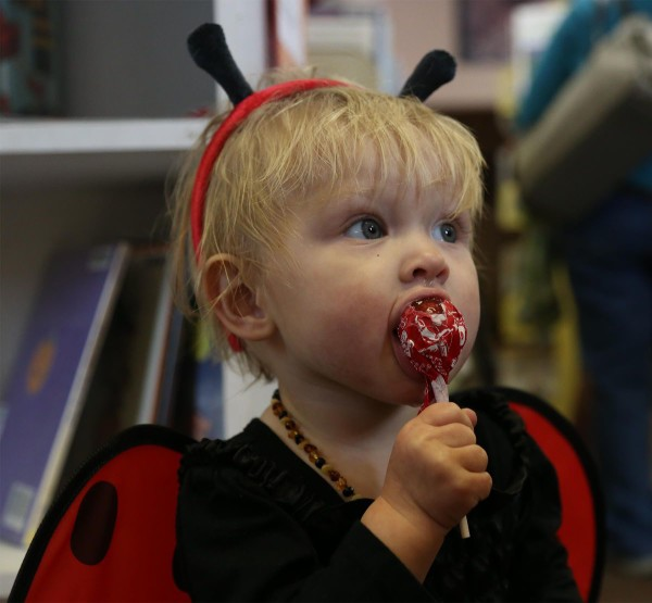 McKenzie Floch, daughter of Wade and Danae Floch, enjoys a Halloween treat during a story hour at the St. Maries Public Library Tuesday.