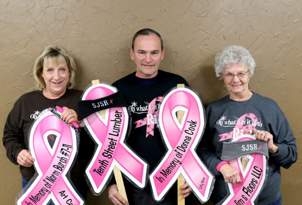 Paula Spooner, Lou Epler, and Dale Hill display memorabilia for the Breast Cancer Snowmobile Ride.