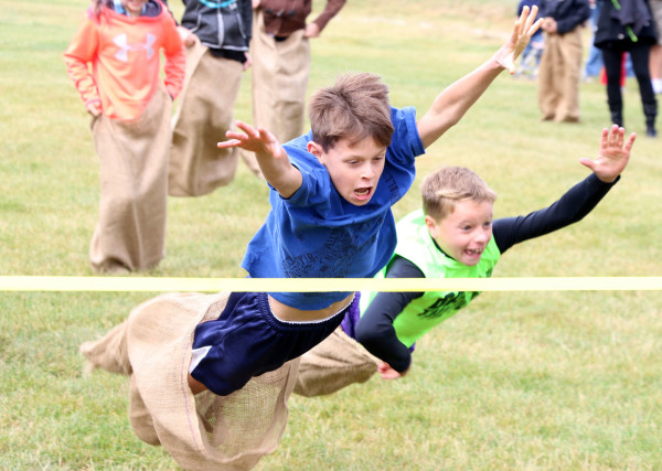 Lance Hamblin and Jared Badgett dive for the finish line in the sack race during the Junior Olympics.